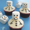 chocolate cupcakes with white frosting and marshmallows decorated to look like snowmen